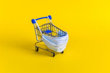 Blue shopping cart with medical mask for virus protection on yellow background. Creative concept of healthcare and safe shopping on coronavirus quarantine